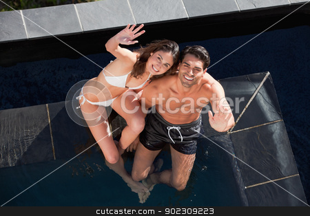 Above view of a smiling couple waving at the camera stock photo, Above view of a smiling couple waving at the camera in a swimming pool by Wavebreak Media