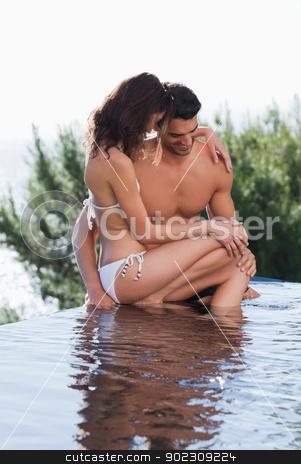 Portrait of a couple cuddling stock photo, Portrait of a couple cuddling in a swimming pool by Wavebreak Media