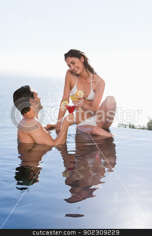 Portrait of a young couple having a cocktail stock photo, Portrait of a young couple having a cocktail in a swimming pool by Wavebreak Media