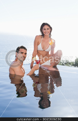 Portrait of a smiling couple having a cocktail stock photo, Portrait of a smiling couple having a cocktail in a swimming couple by Wavebreak Media