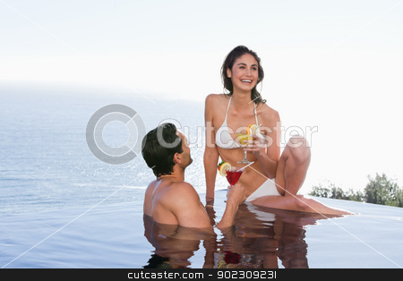 Couple having a cocktail stock photo, Couple having a cocktail in a swimming pool by Wavebreak Media