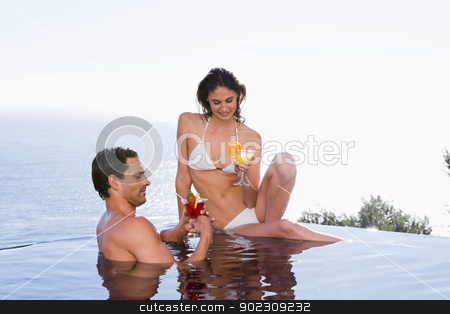 Young couple having a cocktail stock photo, Young couple having a cocktail in a swimming pool by Wavebreak Media