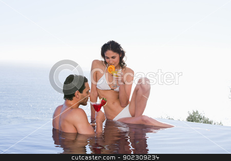 Charming couple having a cocktail stock photo, Charming couple having a cocktail in a swimming pool by Wavebreak Media