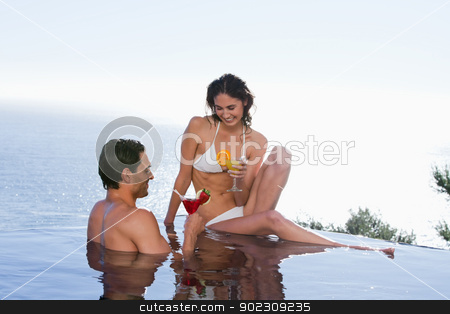 Happy couple having a cocktail stock photo, Happy couple having a cocktail in a swimming pool by Wavebreak Media