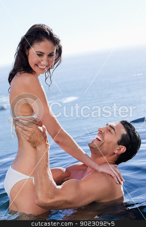 Portrait of a playful couple relaxing stock photo, Portrait of a playful couple relaxing in a swimming pool by Wavebreak Media