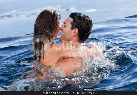 Couple cuddling each other stock photo, Couple cuddling each other in a swimming pool by Wavebreak Media