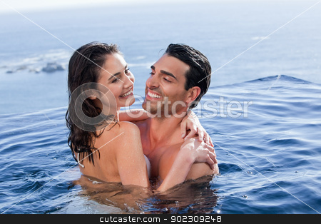 In love couple cuddling each other stock photo, In love couple cuddling each other in a swimming pool by Wavebreak Media