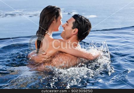 Joyful couple cuddling each other stock photo, Joyful couple cuddling each other in a swimming pool by Wavebreak Media