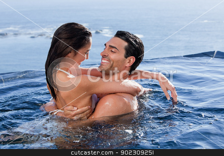 Delighted couple cuddling each other stock photo, Delighted couple cuddling each other in a swimming pool by Wavebreak Media