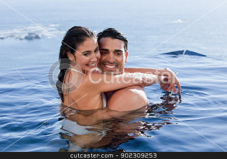 Beautiful couple cuddling each other stock photo, Beautiful couple cuddling each other in a swimming pool by Wavebreak Media