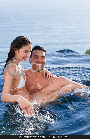 Portrait of a man holding his wife stock photo, Portrait of a man holding his wife in a swimming pool by Wavebreak Media