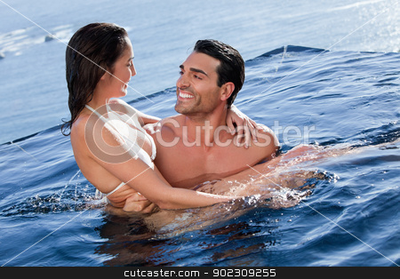 Man holding his wife stock photo, Man holding his wife in a swimming pool by Wavebreak Media