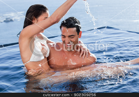 Man holding his playful wife stock photo, Man holding his playful wife in a swimming pool by Wavebreak Media
