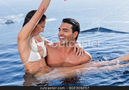 Man holding his playful girlfriend stock photo, Man holding his playful girlfriend in a swimming pool by Wavebreak Media
