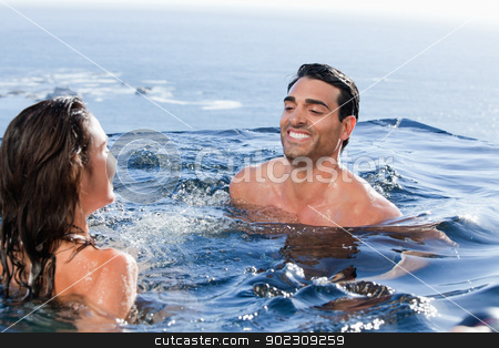Smiling couple playing stock photo, Smiling couple playing in a swimming pool by Wavebreak Media