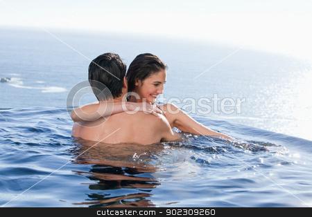 Smiling couple playing together stock photo, Smiling couple playing together in a swimming pool by Wavebreak Media