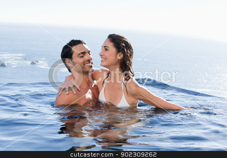 Couple playing together stock photo, Couple playing together in a swimming pool by Wavebreak Media