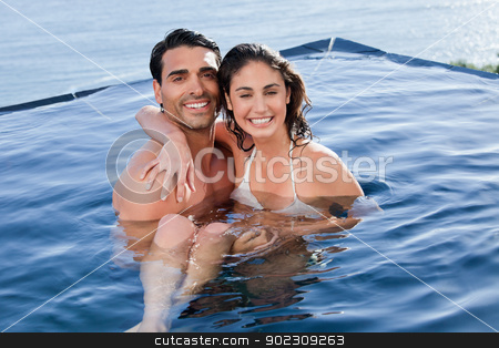 Young couple playing together stock photo, Young couple playing together in a swimming pool by Wavebreak Media
