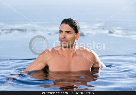 Handsome man relaxing stock photo, Handsome man relaxing in a swimming pool by Wavebreak Media