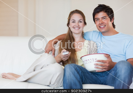 Young couple watching television while eating popcorn stock photo, Young couple watching television while eating popcorn in their living room by Wavebreak Media