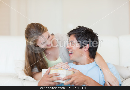 Woman offering a present to her boyfriend stock photo, Woman offering a present to her boyfriend in their living room by Wavebreak Media