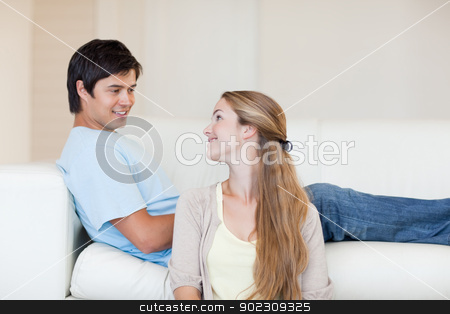 Couple looking at each other stock photo, Couple looking at each other in their living room by Wavebreak Media