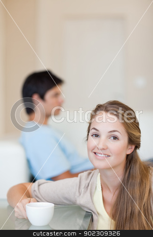 Portrait of a woman having a cup of tea while her husband is sit stock photo, Portrait of a woman having a cup of tea while her husband is sitting on a sofa in their living room by Wavebreak Media