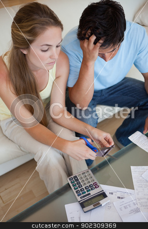Portrait of a couple cutting their credit card stock photo, Portrait of a couple cutting their credit card in their living room by Wavebreak Media