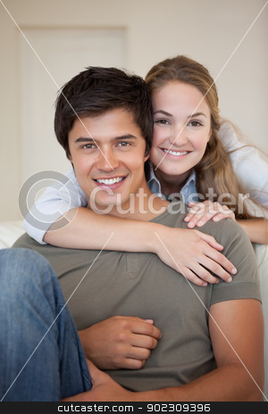 Portrait of a couple hugging stock photo, Portrait of a couple hugging in their living room by Wavebreak Media