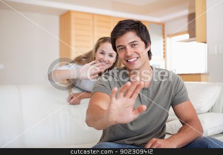 Couple waving at the camera stock photo, Couple waving at the camera in their living room by Wavebreak Media