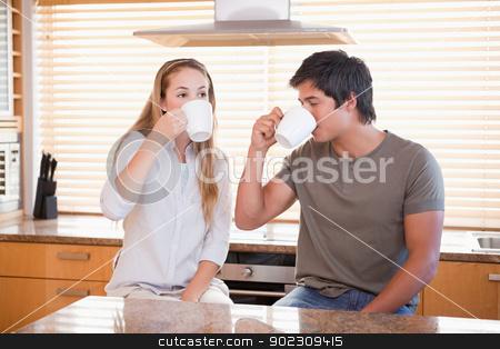 Young couple having a cup of tea stock photo, Young couple having a cup of tea in their kitchen by Wavebreak Media