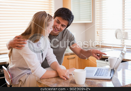 Couple having tea while using a laptop stock photo, Couple having tea while using a laptop in their kitchen by Wavebreak Media