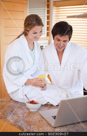 Portrait of a young couple having breakfast while using a laptop stock photo, Portrait of a young couple having breakfast while using a laptop in their kitchen by Wavebreak Media