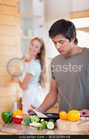Portrait of a man cooking while his wife is washing the dishes stock photo, Portrait of a man cooking while his wife is washing the dishes in their kitchen by Wavebreak Media