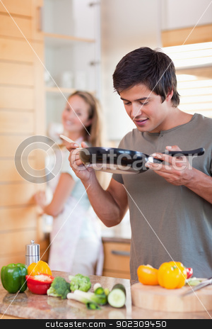 Portrait of a man cooking while his fiance is washing the dishes stock photo, Portrait of a man cooking while his fiance is washing the dishes in their kitchen by Wavebreak Media