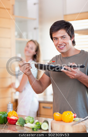 Portrait of a young man cooking while his wife is washing the di stock photo, Portrait of a young man cooking while his wife is washing the dishes in their kitchen by Wavebreak Media
