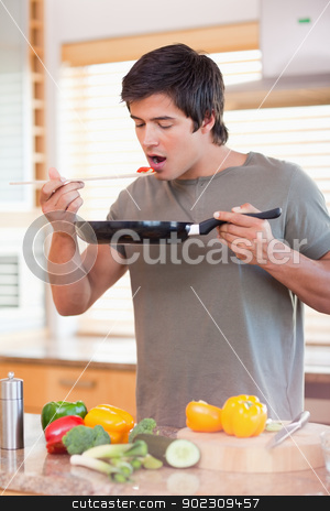 Portrait of a man tasting his meal stock photo, Portrait of a man tasting his meal in his kitchen by Wavebreak Media