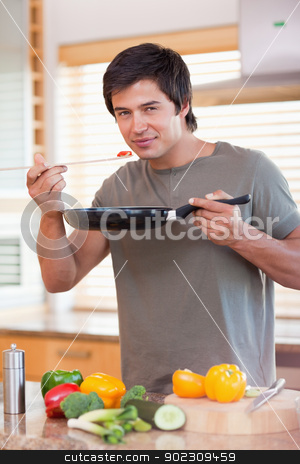 Portrait of a handsome man tasting his meal stock photo, Portrait of a handsome man tasting his meal in his kitchen by Wavebreak Media