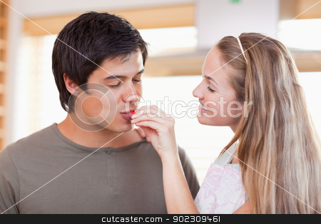 Man tasting the meal of her fiance stock photo, Man tasting the meal of her fiance in their kitchen by Wavebreak Media