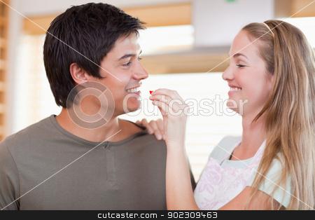 Woman feeding her husband stock photo, Woman feeding her husband in their kitchen by Wavebreak Media