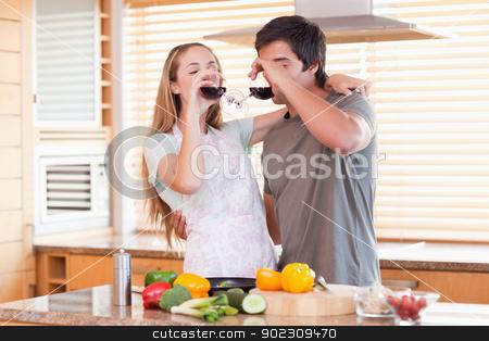 Lovely couple drinking red wine stock photo, Lovely couple drinking red wine in their kitchen by Wavebreak Media