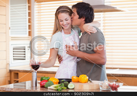 Lovely couple drinking red wine while kissing stock photo, Lovely couple drinking red wine while kissing in their kitchen by Wavebreak Media