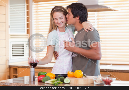Lovely couple drinking wine while kissing stock photo, Lovely couple drinking wine while kissing in their kitchen by Wavebreak Media