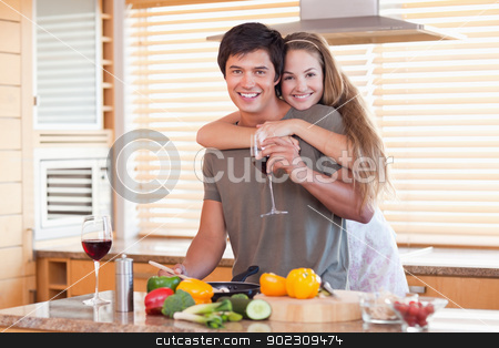 Lovely couple drinking red wine while hugging stock photo, Lovely couple drinking red wine while hugging in their kitchen by Wavebreak Media