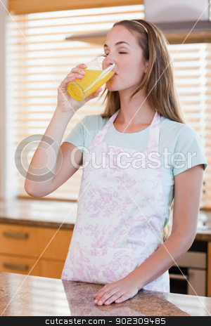 Portrait of a beautiful woman drinking orange juice stock photo, Portrait of a beautiful woman drinking orange juice in her kitchen by Wavebreak Media