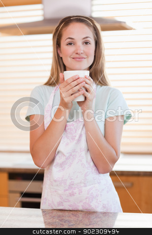 Portrait of a woman drinking a cup of tea stock photo, Portrait of a woman drinking a cup of tea in her kitchen by Wavebreak Media