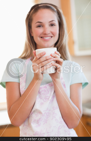 Portrait of a woman drinking a cup of coffee stock photo, Portrait of a woman drinking a cup of coffee in her kitchen by Wavebreak Media