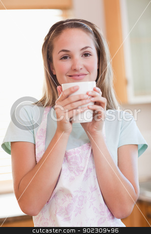 Portrait of a quiet woman drinking a cup of coffee stock photo, Portrait of a quiet woman drinking a cup of coffee in her kitchen by Wavebreak Media