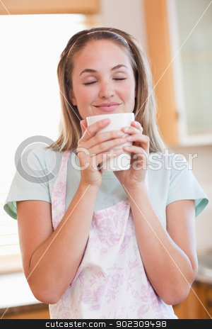 Portrait of a quiet woman drinking a cup of tea stock photo, Portrait of a quiet woman drinking a cup of tea in her kitchen by Wavebreak Media
