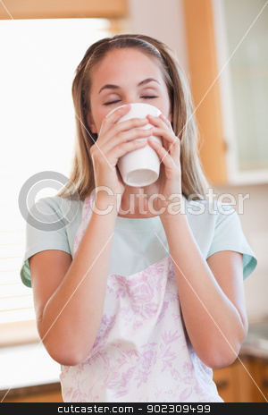 Portrait of a calm woman drinking a cup of tea stock photo, Portrait of a calm woman drinking a cup of tea in her kitchen by Wavebreak Media